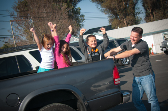 happy man with three kids near a pickup truck they just bought